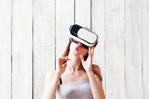 Mujer joven con gafas de realidad virtual, sosteniendo sus manos en la cara, fondo de madera blanca foto