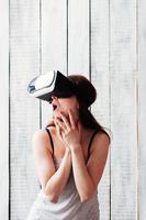 Mujer con gafas de realidad virtual, emocionada, sosteniendo sus manos en la cara, fondo blanco de madera foto