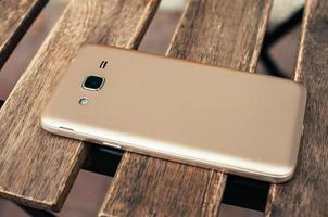 Closeup view of champagne color smart phone, on wooden table photo