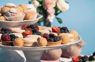 Delicious sweet buffet with cupcakes, macaroons, other desserts, blue backdrop photo