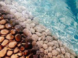 Big pebbles and stones under blue transparent water on the beach photo