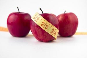 three apples with measuring tape table photo