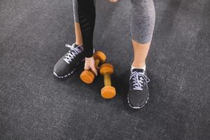 low section view woman picking dumbbell gym photo