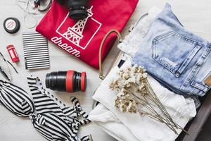 overhead view travelling bag with female outfits flowers photo