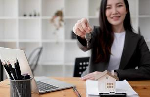 Close up focus on keys, smiling woman realtor selling apartment, offering to client, showing at camera, holding documents, contract, making purchasing deal, real estate agent, mortgage or rent photo