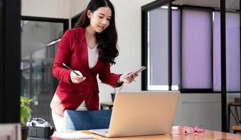 Smiling Asian woman holding mobile phone with fist hand and excited for success in office photo