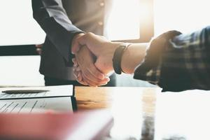 Focus on the congratulatory handshake. The real estate agent agrees to buy the home the customer at the agent's office. concept agreement. photo