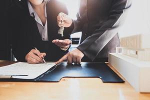 Real estate agents agree to buy a home and give keys to clients at their agency's offices. Concept agreement. photo