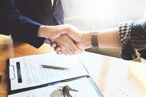 Focus on the congratulatory handshake. The real estate agent agrees to buy the home and hand the keys to the customer at the agent's office. conceptual agreement. photo