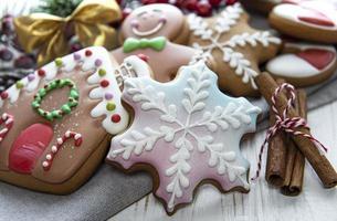 Pan de jengibre navideño con adornos navideños en madera blanca foto