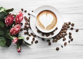 A cup of coffee with heart pattern on a table photo