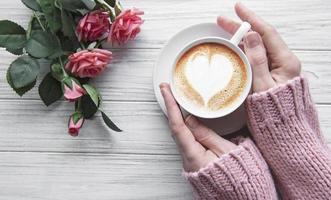 mujer que sostiene la taza de café foto