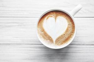 una taza de café con patrón de corazón en una mesa foto
