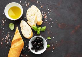 Sliced fresh crusty baguette with olive and spices photo