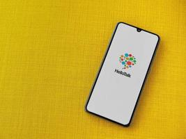 HelloTalk - Language learning app launch screen with logo on the display of a black mobile smartphone on a yellow fabric background photo