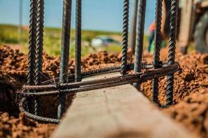 Varilla de acero utilizada para la construcción de postes con hormigón armado en un agujero en el suelo en el sitio de construcción foto