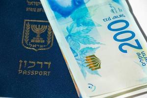 Stack of israeli money bills of 200 shekel and israeli passport - Top view photo