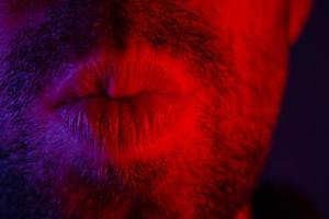 Macro close up on man with seductive facial expression pulled his lips to give a kiss photo
