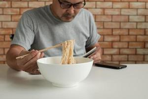 Asian male worker reads an appointment book while eating instant noodles in white bowl with chopsticks on table in brick wall background office during a lunchtime break, a hastily unhealthy lifestyle. photo