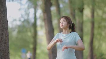 Asian girl listening to music and stretching outdoors video