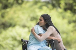 nieta hablando con su abuela sentada en silla de ruedas, concepto alegre, familia feliz foto