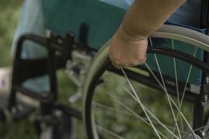 Cerrar solitaria anciana sentada en silla de ruedas en el jardín en el hospital foto