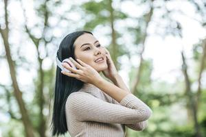 Asian woman listening favorite music on headphones. Happy time and relax. photo