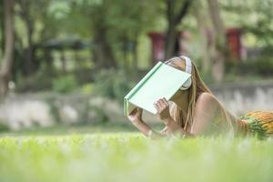 Asian woman listening favorite music on headphones and reading a book. Happy time and relax. photo