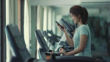 Asian girl walking on the treadmill and listening to music at the gym video