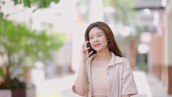 Asian teenage girl talking on the phone with her friends at the shopping mall video