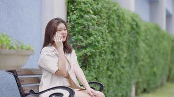adolescente asiatique parlant au téléphone avec ses amis au centre commercial video
