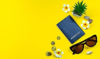 Flatlay accessories for summer vacation. Travel planning. Passport, money, sunglasses on a yellow background. photo