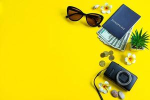 Set of stylish accessories for your summer vacation. Summertime travel. Passport, sunglasses, backpack and money on yellow background. photo