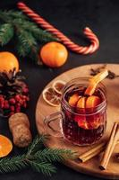 Hot mulled wine in glass cup on dark background. Warm Christmas drink with spices and fruits. photo
