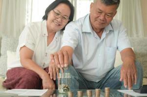 Las parejas asiáticas mayores se sientan en el sofá. ponen monedas en un frasco para planificar sus ahorros. foto
