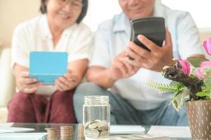 ancianas y hombres asiáticos se sientan en el sofá, hacen planes financieros. foto