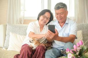 mujeres y hombres asiáticos están sentados en el sofá. están sosteniendo un teléfono inteligente. están sonriendo con una videollamada. foto