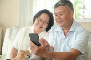 hombres y mujeres mayores están usando su teléfono inteligente en el sofá. foto