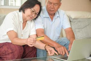 Asian women and men are sitting on the sofa. They are using laptops and consult online payments with credit card. photo