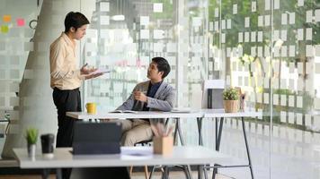 dos hombres de negocios jóvenes están discutiendo el trabajo para presentar a los clientes en una oficina moderna. foto