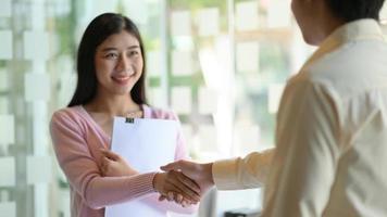 hombres y mujeres jóvenes se dan la mano para felicitar y sonreír felizmente en la oficina moderna. foto