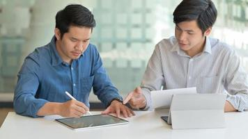 dos hombres asiáticos están usando la tableta para crear su trabajo para presentar a los clientes en una oficina contemporánea. foto