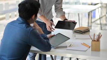 dos hombres asiáticos usando una tableta. consultaron el trabajo para presentar a los clientes en una oficina contemporánea. foto