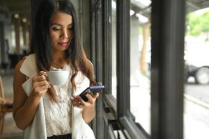 Asian woman in a white dress holding a coffee cup in hand is using a mobile phone. photo