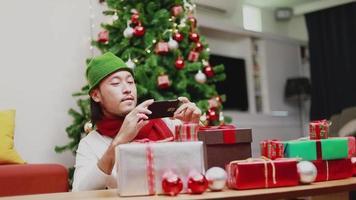 hommes asiatiques prenant une boîte-cadeau photo sur un smartphone. video