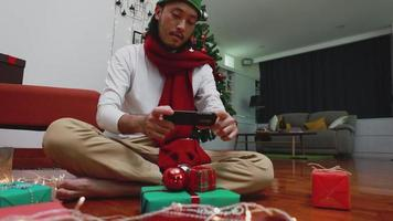 Asian man using mobile taking a photo gift box. video