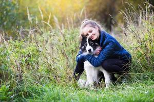 Girl sits hugging with her dog photo