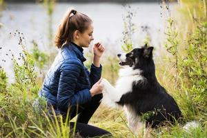 Cute girl in a blue jacket sits in front of her dog photo
