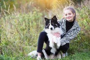 Attractive girl sitting next to her dog photo