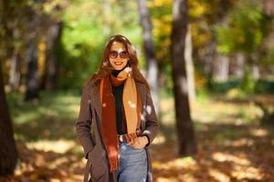 Beautiful young woman walks in the autumn forest photo